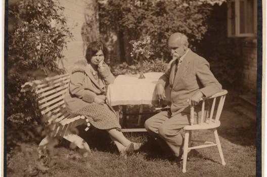 Rainis un Aspazija vasrnīcas dārzā. Abi domīgi sēž pie galda, skatās sāņus. Foto: Olīvs Mētra