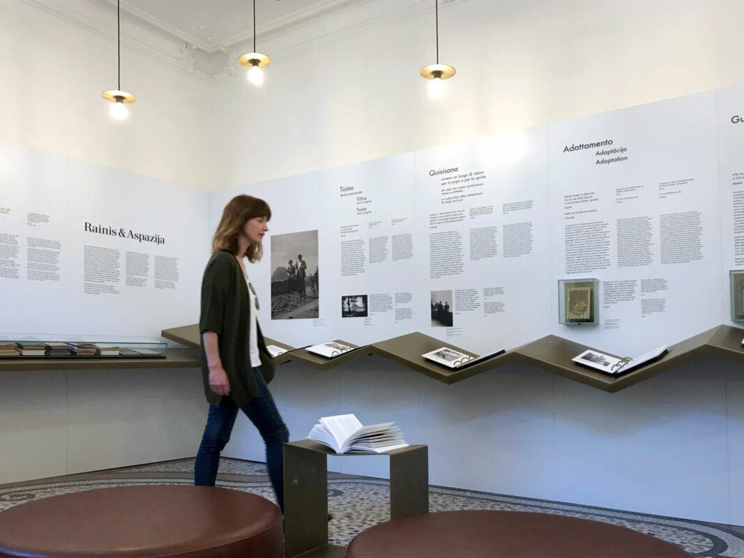 Sieviete pastaigājas pa muzeja ekspozīcijas telpu.