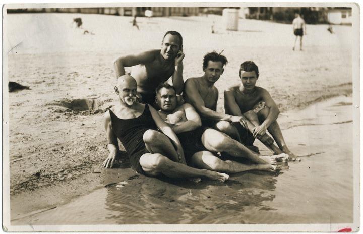 Rainis Rīgas jūrmalā kopā ar Robertu Vizbuli, Olīvu Mētru, Vili Draudziņu un Aleksandru Zvaigzni. Vīrieši pozē fotogrāfam, guļot un sēžot jūras krastā, ap kājām viļņojas ūdens. 1929. gada augusts. Foto: Olīvs Mētra