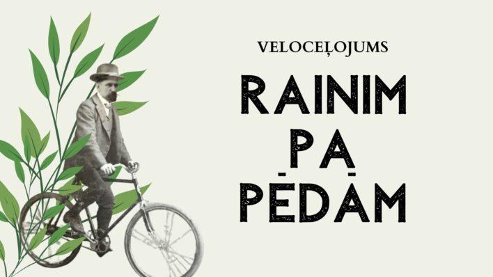 """Afišā attēlos Rainis, kurš brauc ar riteni, aiz viņa - augu attēls. Teksts: Velobrauciens """"Rainim pa pēdām"""""""