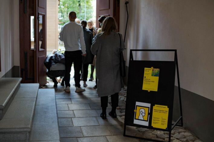 """Ieeja Raiņa un Aspazijas mājā. Vārtrūmē stāv vairāki cilvēki un rindā gaida ieeju muzeja pagalmā. Priekšplānā afišu statīvs ar trīs dzeltenām afišā - viena no tām ir mākslas festivāla """"Survival Kit 12"""", otra vēsta, ka muzejā jāliek sejas maska, trešā informē par drošu muzeja apmeklējumu pandēmijas laikā"""